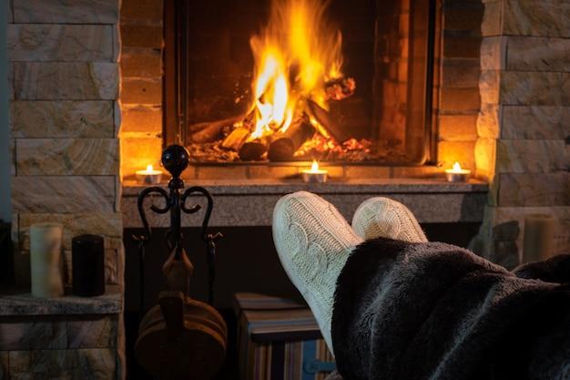 Женские ножки у камина зажжены в уютной домашней обстановке.