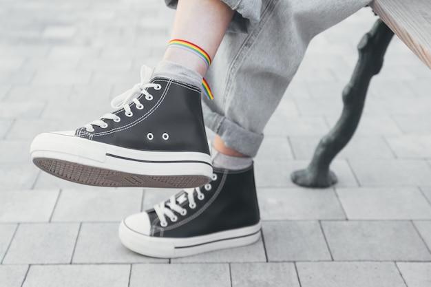 Ноги женщины в черно-белых кроссовках с браслетом гей-прайд на щиколотке сидят на скамейке с ненасыщенными цветами