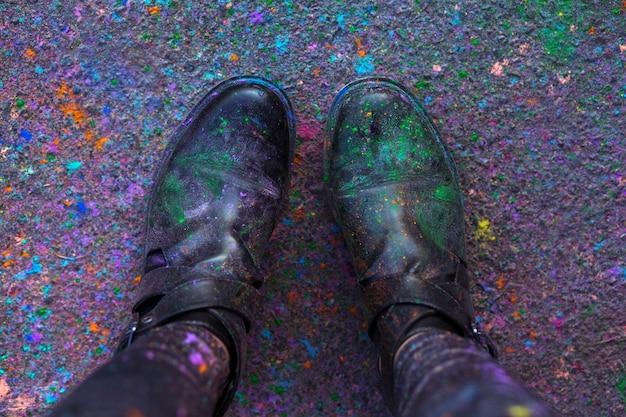 Ноги женщины в черных сапогах, покрытых сухой краской холи на фоне асфальта