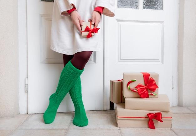 Ноги женщины в зеленых носках стоят возле подарков