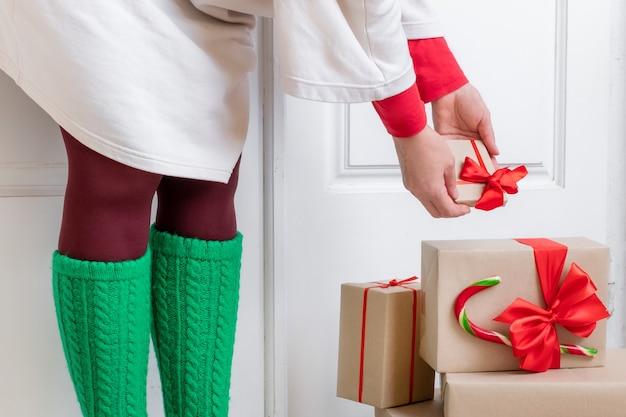 Ноги женщины в зеленых носках стоят у белой двери с подарками накануне праздников рождества и нового года.