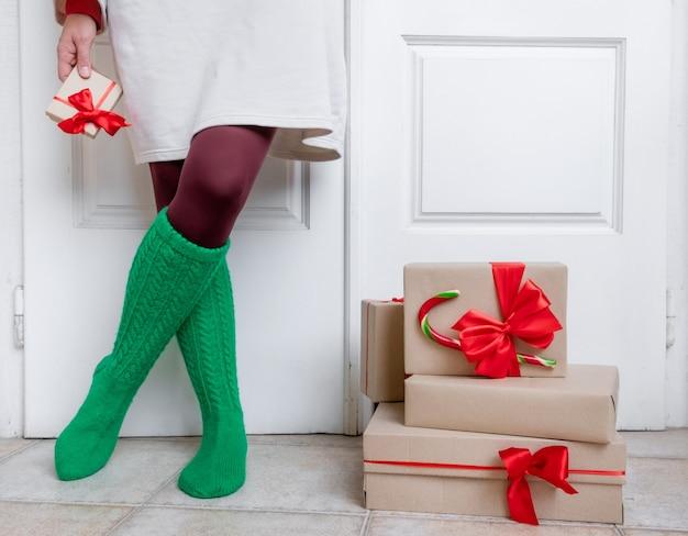 緑の靴下を履いた女性の足は、クリスマスと新年の休日の前夜にギフト付きの白いドアの近くに立っています。