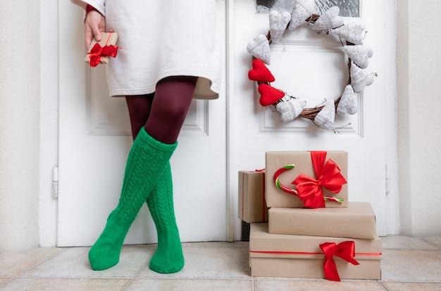 緑の靴下の女性の足は、ギフトと白いドアの近くに立っています