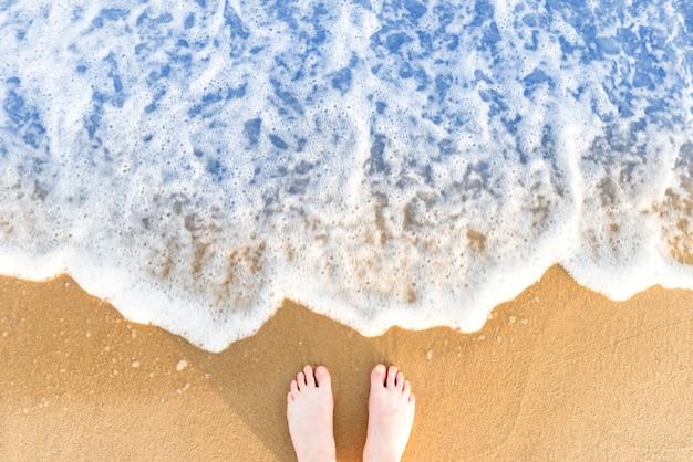 Ноги женщины на желтом песке пляжа с морской волной и белой пеной