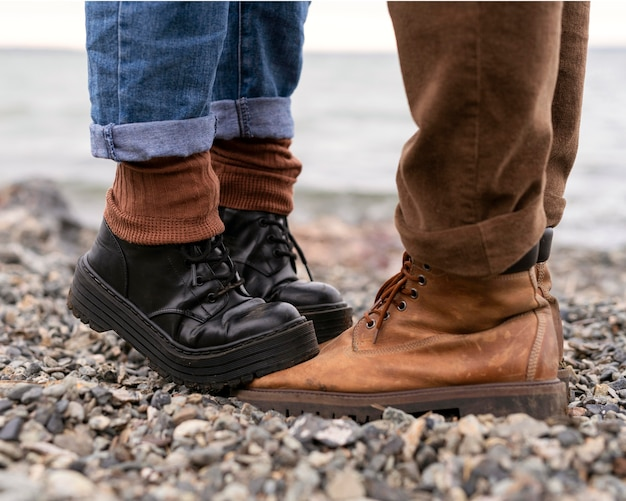 Woman's feet stepping on boyfriend's boots