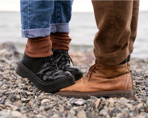 彼氏のブーツを踏む女性の足