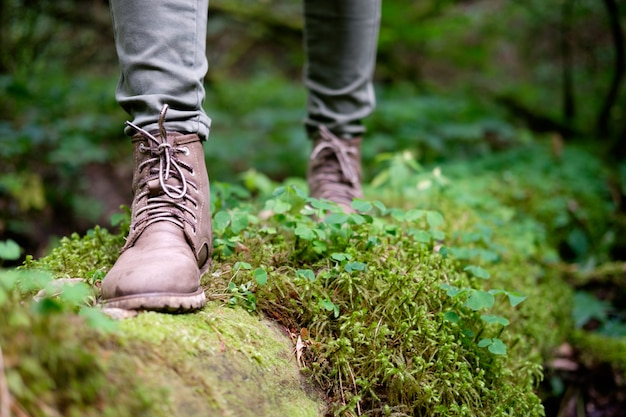 Woman's feet in travel boots a mossy log in the forest. travel concept.