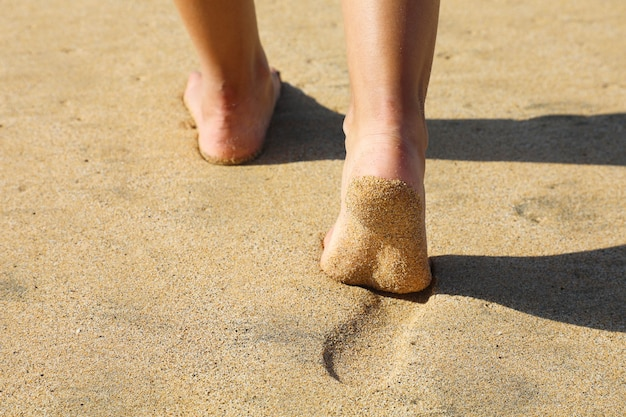 Ноги женщины ходят по песку, оставляя следы