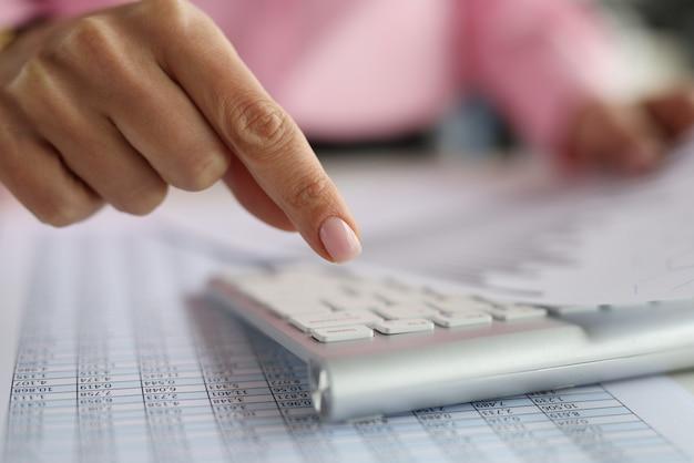 컴퓨터 키보드 위의 여성의 손가락에는 재무 지표가있는 문서가 포함되어 있습니다. 회계 서비스 개념