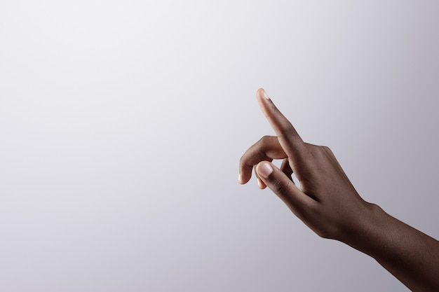 Woman's finger pointing on gray border background