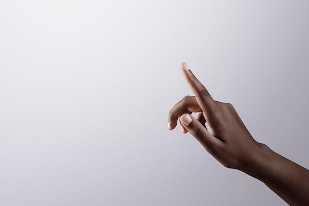 灰色の境界線の背景を指す女性の指