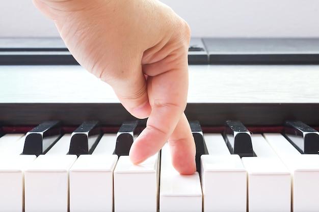 피아노 키를 가리키는 여자의 손가락.