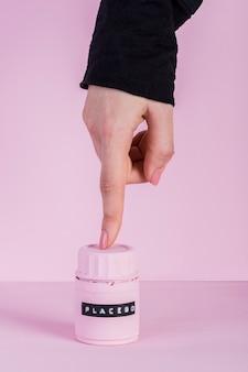Woman's finger touching placebo pills bottle