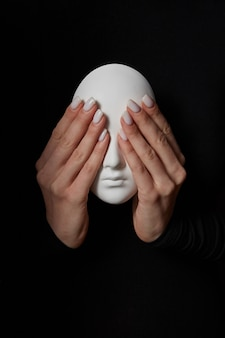 Woman's fingers close eyes of gypsum mask face on a black wall. see no evil. concept three wise monkeys. place for text.