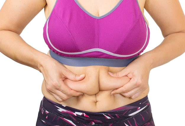 Пальцы женщины измеряют ее жир на животе