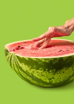 Woman's fingers touch inside organic ripe fresh watermelon's puree