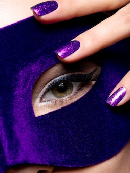 Woman's fingers with blue nails about eye.