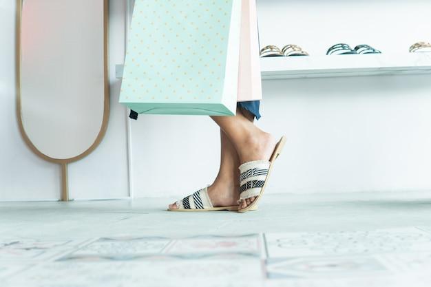 Женская нога и хозяйственная сумка в торговом центре
