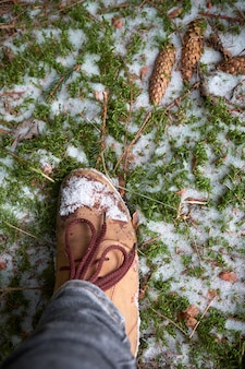 Woman's foot in travel boots on a mossy snowy ground in winter forest. travel concept.