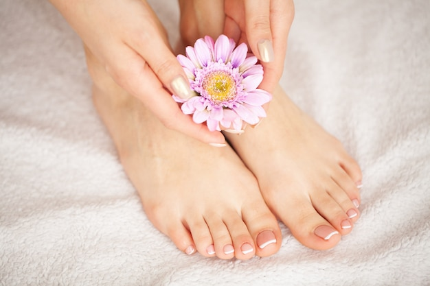 Woman's french pedicure. close up woman hands touching long legs, soft skin. hair removal