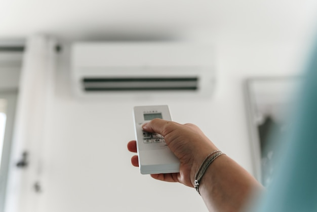 Woman's hand activating the air conditioner with the remote control.
