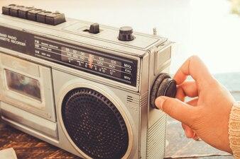 Woman's hand adjusting button vintage radio