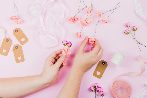 Woman's hand arranging the fake flowers with ribbon and tag on pink backdrop