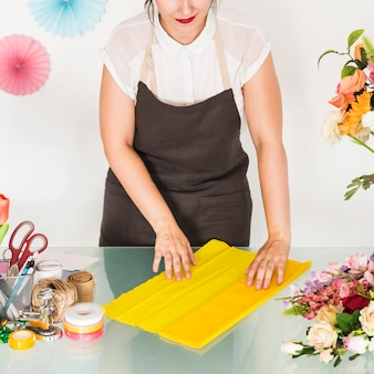 Woman's hand arranging yellow cloth for making flower bouquet on desk