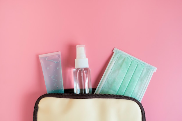 外科用フェイスマスク、アルコールハンドジェル付きの女性のハンドバッグ。コピースペースとピンクの背景の医療衛生アイテム。保護covid-19、コロナウイルス拡散。ヘルスケアの概念。平面図、フラットレイアウト