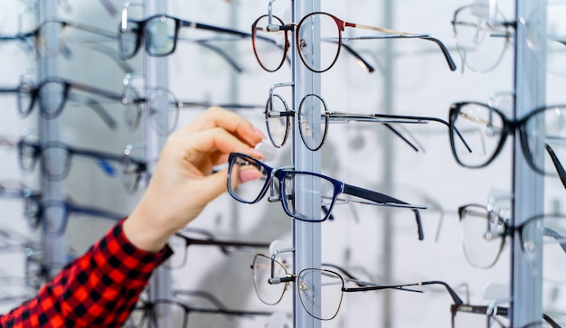 Woman's hand chooses glasses. presenting spectacles. row of glasses at an opticians. eyeglasses shop. stand with glasses in the store of optics.