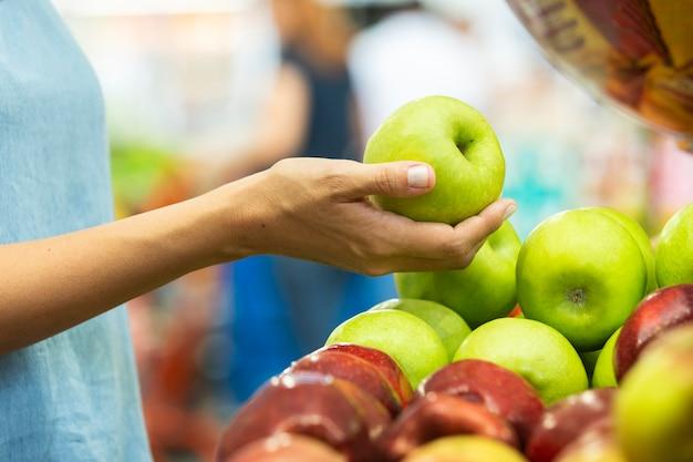 スーパーマーケットで青リンゴを選ぶ女性の手。