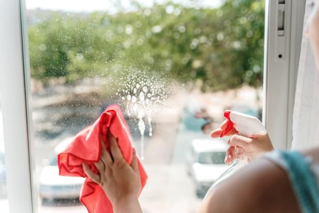 Женская рука чистит оконное стекло тряпкой и жидкостью для мытья окон.