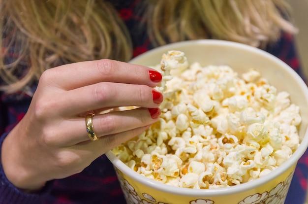 Женская рука крупным планом, поднимая попкорн.