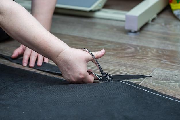 Женская рука ножницами режет черный укрывной материал на полу в доме