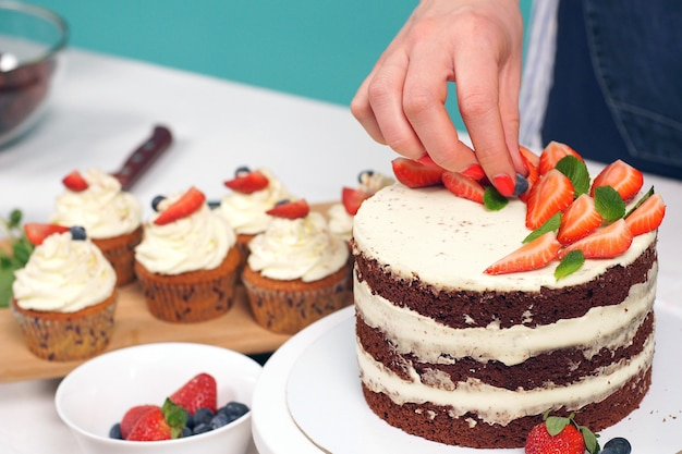 女性の手がおいしいストロベリーケーキを飾るクローズアップ