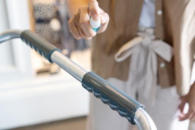 ボトルからアルコールを噴霧することによって空港のトロリーを消毒する女性の手、ヘルスケアの概念。