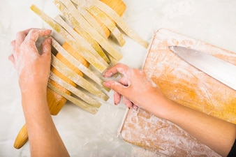 Woman's hand drying pasta on rolling pin