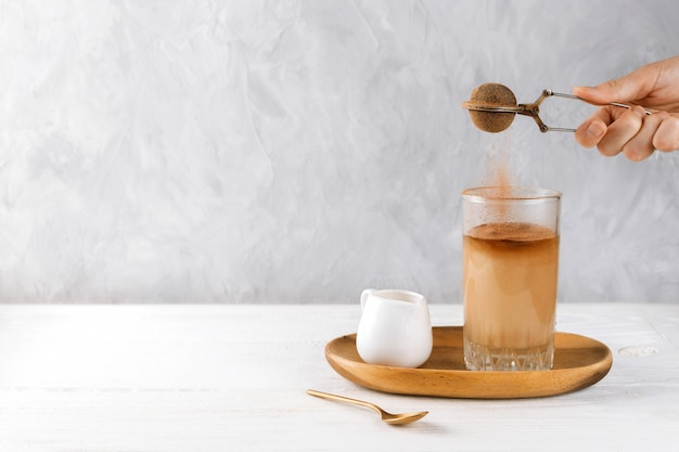 Woman's hand dusting cocoa into vegan iced coffee in a tall glass on a wooden tray, selective focus, copyspace