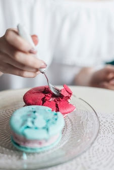 Woman's hand eating ice cream sandwich with fork on glass transparent plate