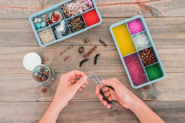 Woman's hand fixing the hook on beads with plier on wooden desk