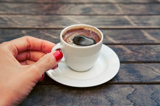 Женская рука складывает небольшую белую чашку крепкого кофе эспрессо на деревянном столе.