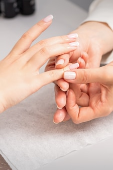 A woman's hand getting a finger massage in a nail salon. manicure treatment at beauty spa