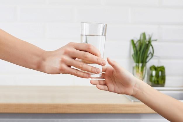 Женская рука дает ребенку стакан очищенной воды. концепция очистки воды