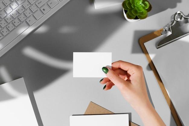Женская рука дает визитку над рабочим столом