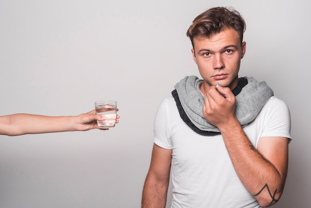 Woman's hand giving glass of water to man taking capsules on gray background