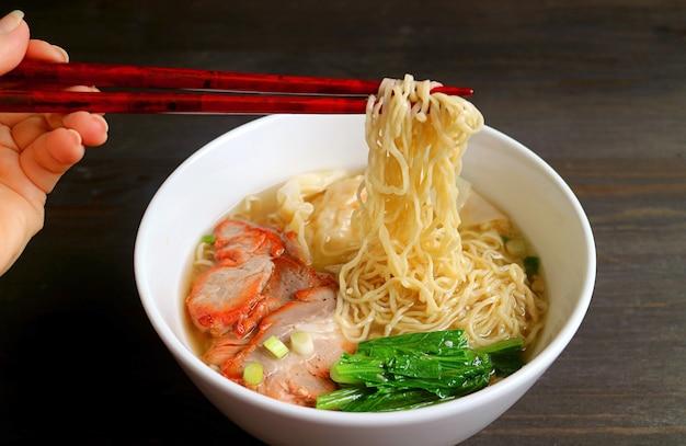Женская рука сжимает восхитительную китайскую яичную лапшу с палочками для еды