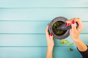 Woman's hand grinding herbs by mortar and pestle