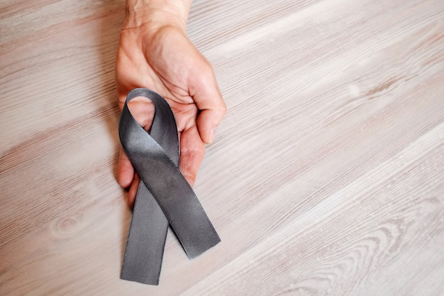 A woman's hand hold a gray ribbon of awareness of parkinsons disease.