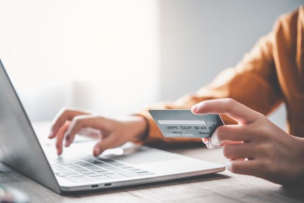 Женская рука кредитной карты и работает на ноутбуке. онлайн-оплата покупок в интернете