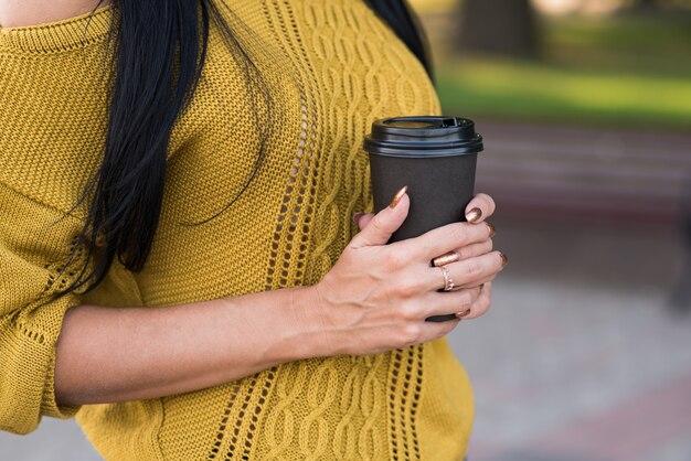 뜨거운 커피 한 잔을 들고 있는 여자의 손을 닫습니다.